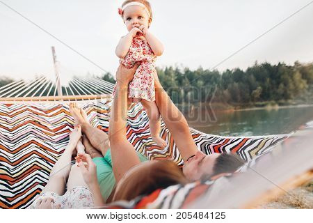 Cute Baby Girl In Stylish Dress With Her Parents Lying In A Hammock Near Lake And Forest On Family V
