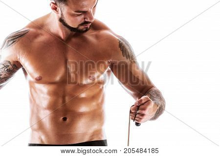 Muscular fitness model posing shirtless over white background. Athletic young man with tattoos standing with resistance band. Strength and motivation concept.