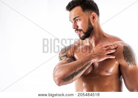 Portrait of handsome fitness male model with tattooed torso. Studio shot of athletic young sexy man posing shirtless. Copyspace