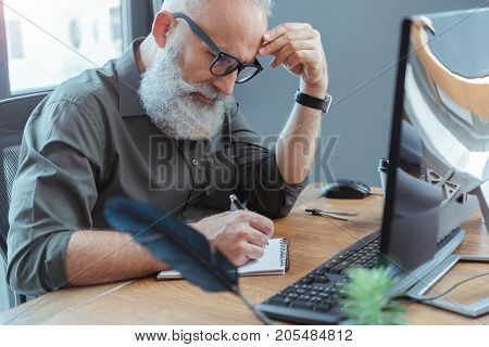 Catch muse. Bearded old poet with glasses is writing in copybook. He is sitting at table with computer and touching his face thoughtfully