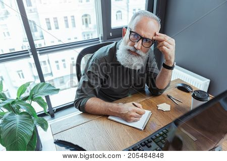 Pensive look. Top view of serious mature bearded writer in glasses is sitting at table with computer and looking at camera thoughtfully while making notes. He is leaning on elbow and touching his face