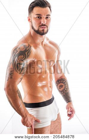 Muscular sexy fitness model posing shirtless over white background. Athletic young man with tattooed torso standing in underwear.