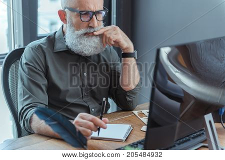 In search of ideas. Focused elderly bearded author is sitting at table and touching his lips while looking at screen of computer with concentration. Copy space in the right side