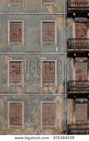 Facade of an old abandoned house in Lisbon Portugal. Structured facade former windows filled with bricks. Decorated balconies.