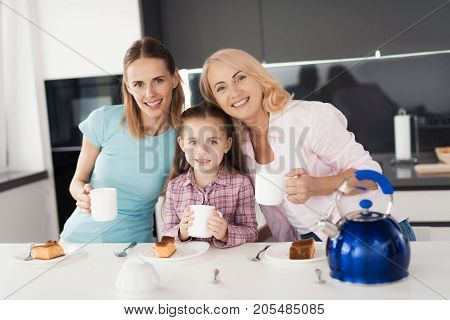 The family is drinking tea. A woman, her mother and daughter are drinking tea and posing in the kitchen. Before them are plates with a homemade pie, in their hands they hold cups of tea