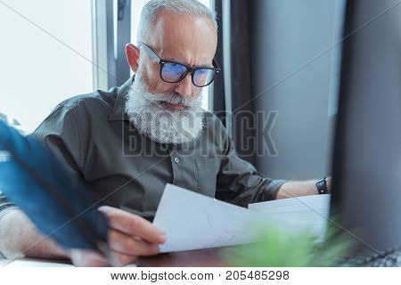 My masterpiece. Serious mature bearded writer in glasses is holding sheets of papers. He is sitting at table thoughtfully