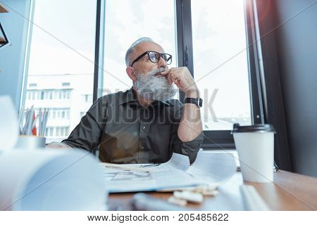 Searching solution. Low angle of serious elderly architect is sitting at table with blueprints and looking aside thoughtfully. He is leaning on desk and touching his lips