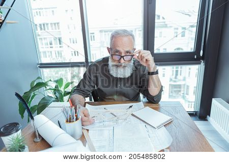 Top view portrait of serious old man is sitting at table with blueprints and looking at camera confidently while holding his glasses. He is working in light office with big window on background