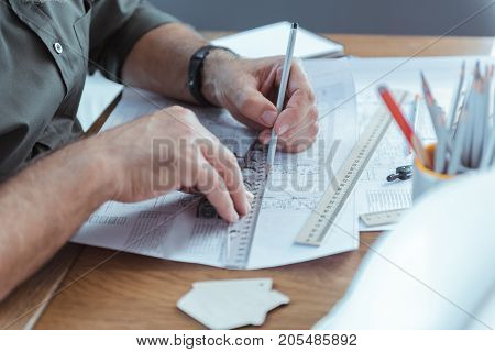 Be accurate. Close-up of pencil and ruler in hands of professional engineer. He is drawing blueprint sketch while sitting at table. Copy space in the right side