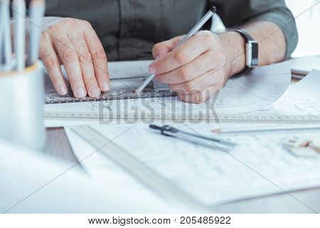 Accurate measurements. Close-up of ruler and pencil in hands of skillful architect. He is working on design plan while sitting at table in office. Selective focus