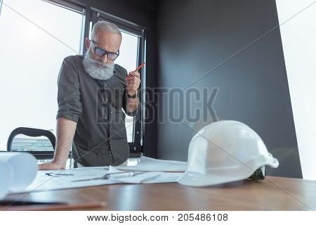 Serious and responsible. Low angle of professional bearded engineer is leaning on table and looking at blueprints with concentration. He is holding pencil while standing against window. Copy space