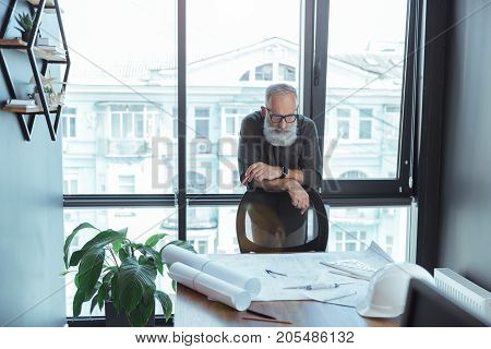 Busy at work. Portrait of skillful old gray-haired man is leaning on chair and looking at his blueprints on table. He is standing in office with big window on background. Copy space in the left side
