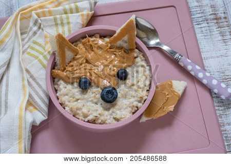 Kids breakfast porridge with fruits and nuts look like a fox