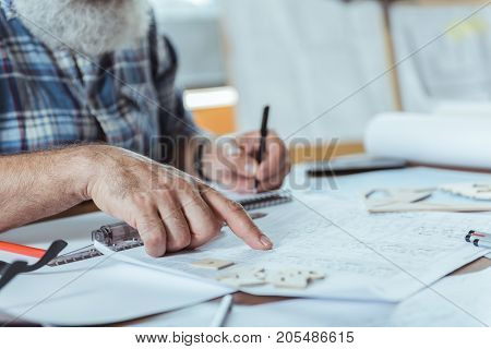 Close-up of hand is pointing on blueprint of bearded gray-haired man who is sitting at working place and taking notes in notebook. Copy space in the right side. Selective focus