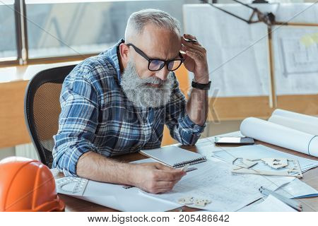 Absorbed in work. Professional elderly architect is sitting at table and looking at sample in his hand with concentration. He is leaning on desk and touching his temple thoughtfully