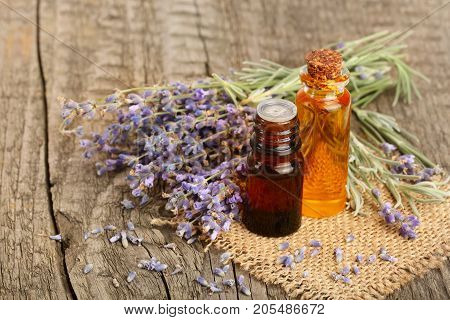 Herbal oil and lavender flowers on old wooden background.