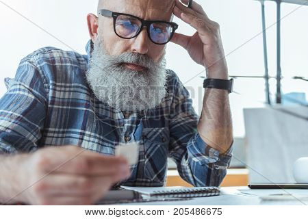 Feeling tired. Selective focus on face portrait of serious engineer in glasses is sitting at desk and looking at sample in his hand with concentration. He is leaning on table and touching his head thoughtfully