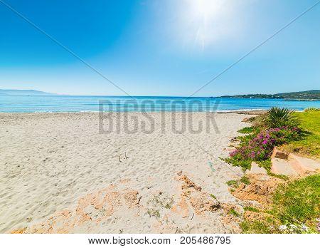 Sun shining over Le Bombarde beach Sardinia