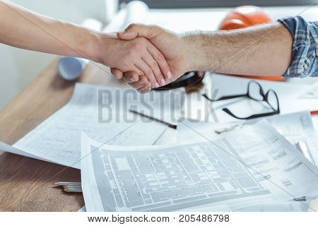 Good deal. Close-up of shaking hands of man and woman. Blueprints, pencils glasses and other things are on desk
