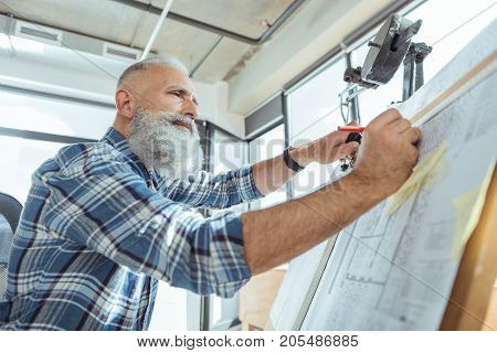 Low angle of serious skillful bearded architect is using professional equipment for making blueprints. He is looking at his project with concentration while doing measurements