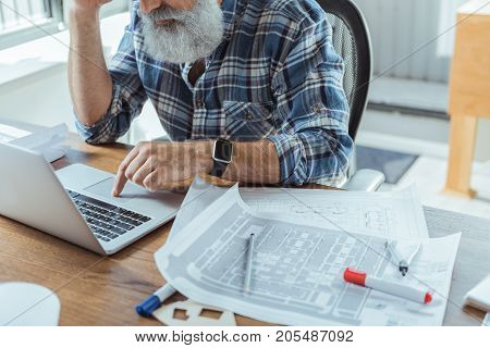 Need fresh idea. Serious old bearded man is leaning elbow on desk and working on laptop thoughtfully. Building plans are on table