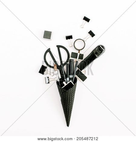 Black waffle cone with office stationery tools. Flat lay top view minimal office concept.
