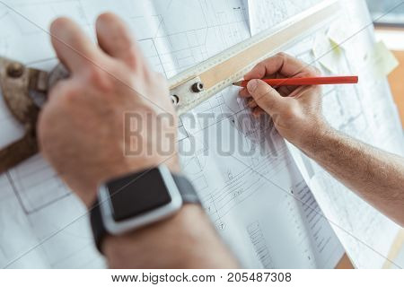 Responsible job. Close-up of arms of professional engineer is making measurements using drawing tool. Focus on hand with smartwatch pencil