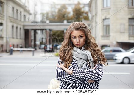 Close up picture of stunning glamourous young female having serious look keeping arms folded and pouting as she has to stand on city street on cold autumn day and wait for her boyfriend who is late