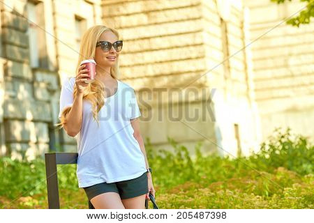 A beautiful young blonde woman standing in the shade next to an old building with her sunglasses on and having a coffee