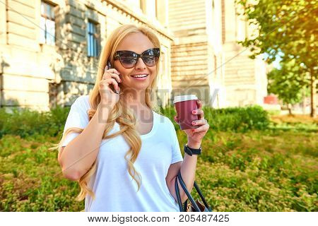 A beautiful young blonde woman standing in the shade next to an old building while talking on the phone and holding a coffee