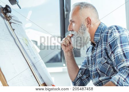 Where is mistake. Profile of serious experienced engineer is sitting near board and looking at blueprints with concentration. He is touching his lips thoughtfully. Copy space in the left side