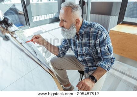 Working on mistake. Top view of qualified elderly engineer is pointing by pencil on design plan and looking at it with concentration