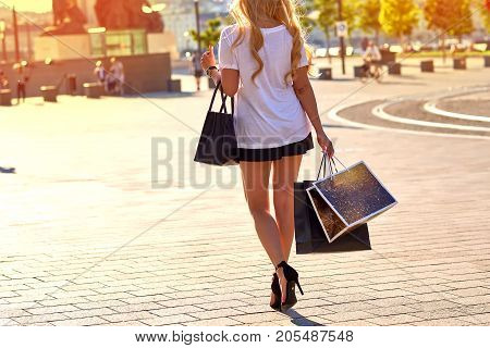 Close up look of paper shopping bags in a young woman hands who is wearing high heels