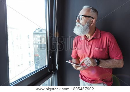 Smart device. Pleasant senior man with beard is using tablet while looking through window thoughtfully. Copy space in the left side