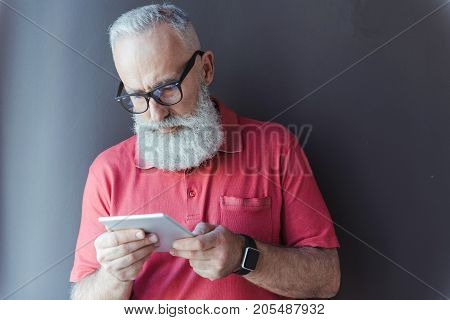 Important news. Serious stylish gray-haired businessman with beard is holding tablet and reading information with concentration. He is standing against gray wall