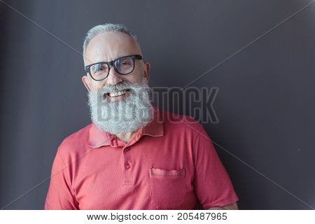 Be positive. Waist-up portrait of happy elderly man with beard is leaning on gray wall and looking at camera with joy. Copy space in the right side