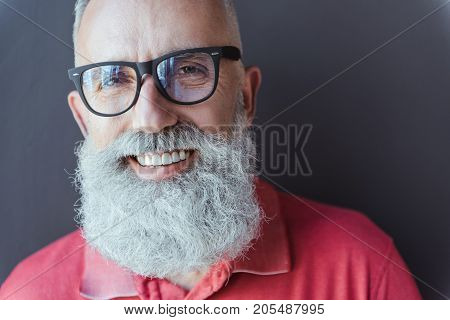 Sharing happiness. Close-up portrait of joyful bearded old man in glasses is looking at camera with wide smile. He is posing against gray wall. Copy space in the right side