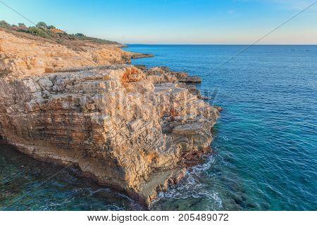Large rocky coastline under blue sky in the ocean