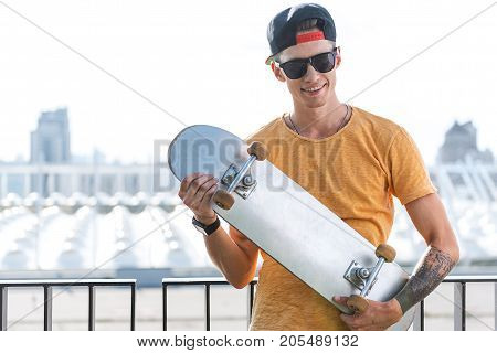 Portrait of cheerful teenager keeping skate in hands at street. He looking at camera. Copy space