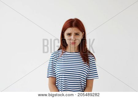 Horizontal studio portrait of upset sad Caucasian teenage girl with red colored hair and pursed lips having disappointed unhappy look frowning and pouting after quarrel or fight with her boyfriend