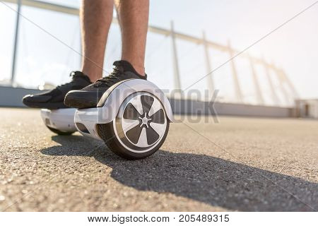 Close up teenager legs situating on gyroboard. He moving on street. Technology concept