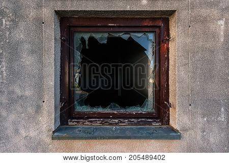 Shattered glass in broken window on abandoned building
