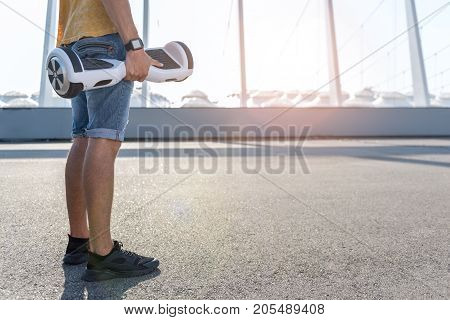 Close up young male legs. He standing on asphalt while keeping gyroboard in arm. Copy space