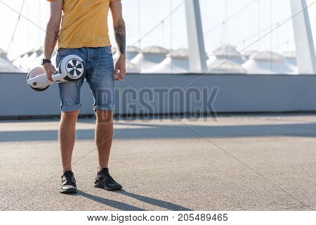 Close up male hand holding digital device. He walking at street during sunny day. Technology concept. Copy space