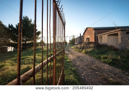 Abandoned houses with large opened rusty gate