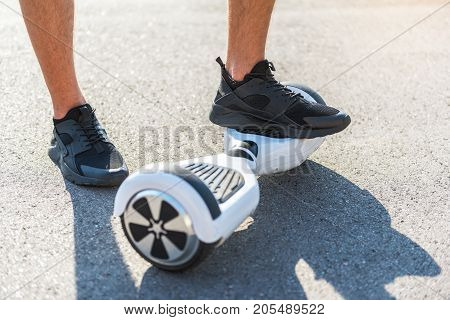 Close up boy leg standing on hoverboard while another situating on asphalt. Digital device concept