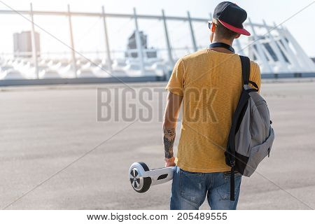 Modern teenager keeping gyroscope in arm while going outdoor. He turning back to camera. Copy space
