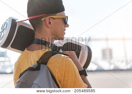 Side view cheerful boy keeping new gyroscooter in arm while going outdoor. Copy space