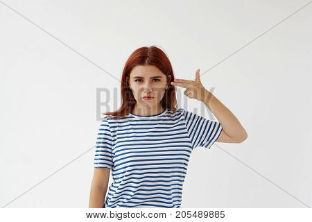 Portrait of beautiful teenage girl wants to kill herself holding fingers at her head. Depressed young female with red dyed hair making pistol sign and poiting at her temple. Depression and suicide