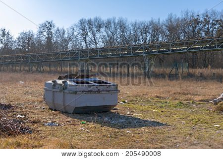 Large trash container on the ground outdoors in forest